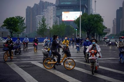 FOTO DE ARCHIVO: Personas con mascarillas circulan en bicicleta por una calle de Wuhan, la ciudad china más afectada por el brote de la enfermedad del nuevo coronavirus (COVID-19), en China, el 14 de mayo de 2020. REUTERS/Aly Song