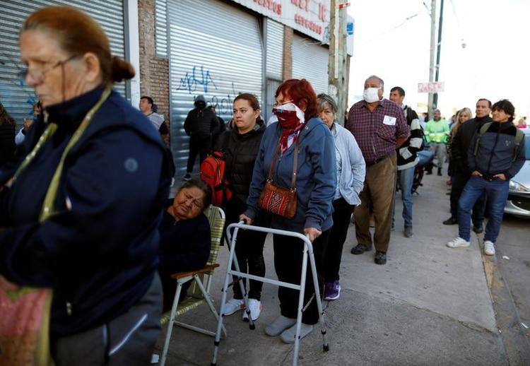 Jubilados y personas con planes de asistencia social hacen cola fuera de un banco (Reuters)