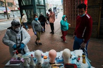 Vivien Grullon, a la izquierda, vende mascarillas, guantes y artículos de limpieza debajo de la estación del tren 7 en la avenida Roosevelt en Jackson Heights, Queens. (Ryan Christopher Jones / The New York Times)