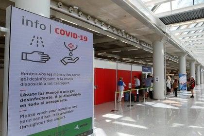 Personas hacen cola frente a un sitio de testeo de COVID-19 en el aeropuerto de Son Sant Joan en Palma de Mallorca, España, 30 de marzo de 2021. (REUTERS / Enrique Calvo)