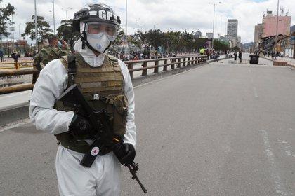 Un soldado con traje vigila una protesta para exigir ayudas dada la cuarentena decretada ante los contagios de COVID-19 en Bogotá (Colombia). EFE/ Carlos Ortega/Archivo