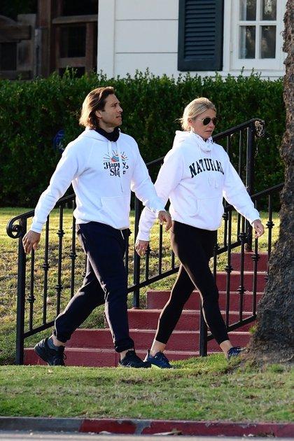 Romántico y deportivo paseo. Gwyneth Paltrow y su marido, Brad Falchuk, caminaron por las calles de su barrio en Brentwood, California. La actriz y el director de televisión lucieron un outfit similiar: zapatillas negras de cuero, pantalones y calzas del mismo color, y buzo blanco con distintas inscripciones
