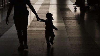 Un ciudadano neozelandés varado con su hijo con una máscara facial llega a bordo de un vuelo de repatriación de vuelta a casa en el aeropuerto internacional Indira Gandhi de Nueva Delhi, India, el jueves 23 de abril de 2020 (Foto AP/Manish Swarup)