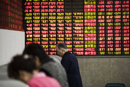 """Investors stand at trading terminals in front of electronic stock boards at a securities brokerage in Shanghai, China, on Friday, Oct. 13, 2017. A number of economic indicators show """"stabilized and stronger growth"""" and the momentum of a 6.9 percent expansion in the first six months of 2017 """"may continue in the second half,"""" People's Bank of China Governor Zhou Xiaochuan said. Photographer: Qilai Shen/Bloomberg"""