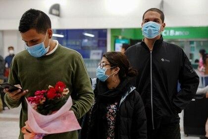 Personas esperando a amigos y familiares en un aeropuerto con mascarillas