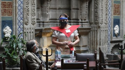 "A waitress at Mexico City's iconic ""Sanborns of the Azulejos"" restaurant, wearing a mask and face shield to curb the spread of the new coronavirus, takes an order from a customer, Wednesday, July 1, 2020. (AP Photo/Eduardo Verdugo)"