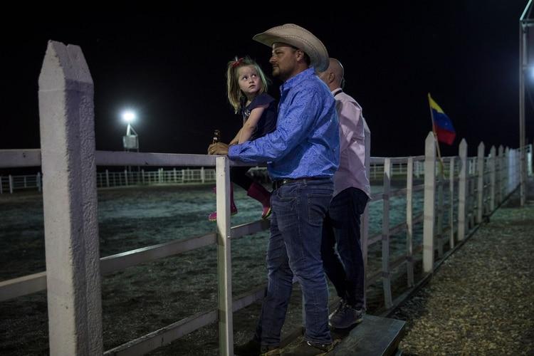 Un hombre y su hija miran a los invitados arriar ganado. Los invitados pintaron un hospital local como un gesto hacia a la comunidad local