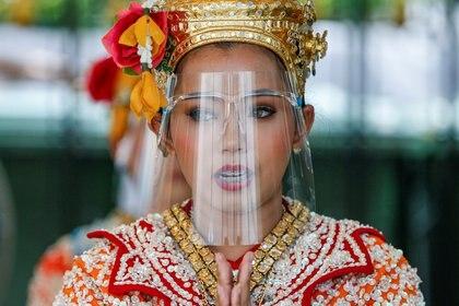 Una artista usa una mascarilla facial de protección durante un show en un templo de Bangkok, Tailandia (Reuters)