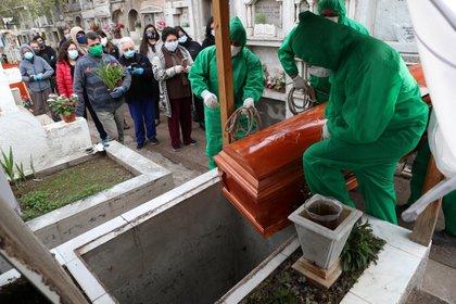 Personal vestido con trajes de protección contra el coronavirus, ejecutan un entierro en Chile