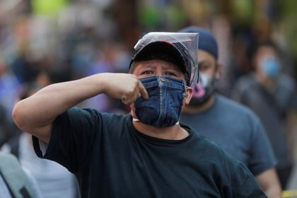 A person wearing a mask walks near the Zocalo Square during the gradual reopening of commercial activities in the city, as the coronavirus disease (COVID-19) outbreak continues, in Mexico City, Mexico July 14, 2020. REUTERS/Henry Romero