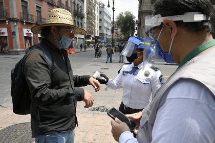 Police and city government workers take the temperature of a man at a pedestrian control that limits the access in groups of 20 people to enter downtown Mexico City on July 6, 2020. - Mexico authorized the reopening of restaurants, shops, street markets and sport complexes but with limited capacity and hours amid the COVID-19 novel coronavirus pandemic. (Photo by ALFREDO ESTRELLA / AFP)