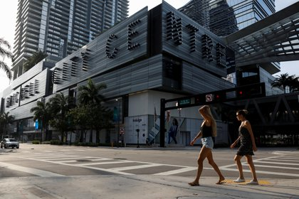 Women walk across an empty avenue during evening rush hour, as the spread of the coronavirus disease (COVID-19) continues, in downtown Miami,  Florida, U.S. April 13, 2020. Picture taken April 13, 2020. REUTERS/Marco Bello