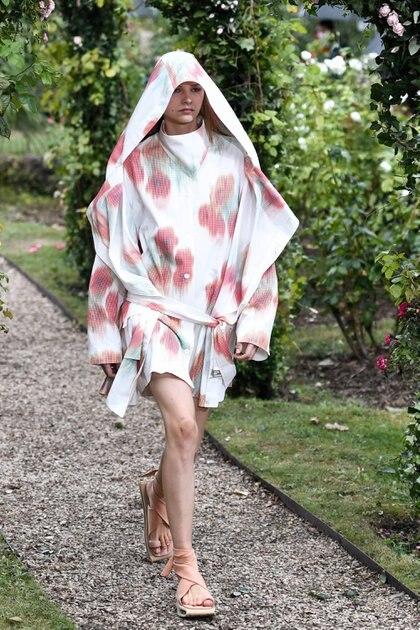 """El clásico estampado """"flower"""" by Kenzo también estuvo presente en la pasarela, con un diseño de vestido oversized con capa y capucha. En los pies, los zapatos las modelos lucieron los nuevos modelos de la colección, las sandalias estilo griegas by Kenzo en diversos colores con tirantes"""