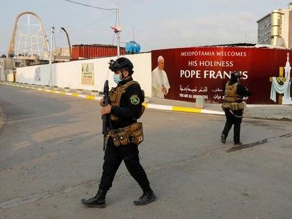 Miembros de seguridad iraquíes caminan cerca de un cartel del Papa Francisco antes de su llegada, en Bagdad, Irak, el 5 de marzo de 2021. REUTERS/Khalid al-Mousily