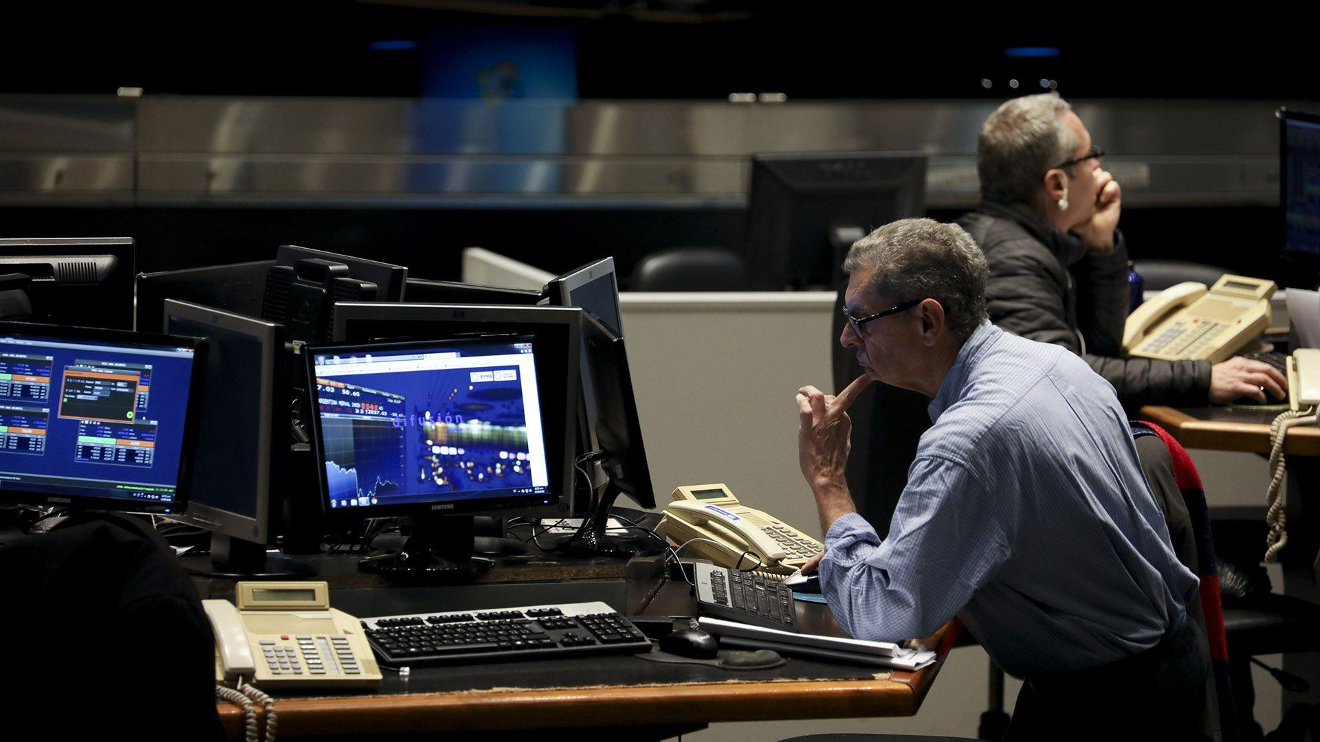Les opérateurs travaillent dans les locaux de la Bourse de Buenos Aires.  (AP)