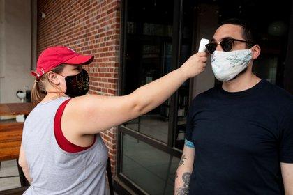 El responsable de un local en Estados Unidos toma la temperatura de uno de sus clientes antes de que ingrese al lugar (Foto: EFE/EPA/MICHAEL REYNOLDS)