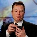 El fundador y CEO de Tesla, Elon Musk, mira su teléfono móvil durante una conferencia de prensa en el Centro Espacial Kennedy en Cabo Cañaveral, Florida (Reuters)