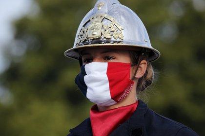 Un bombero, con una mascarilla con los colores de la bandera francesa, antes del desfile del Día de la Bastilla, en la avenida de los Campos Elíseos de París, el 14 de julio de 2020. (AP Foto/Christophe Ena, Pool)