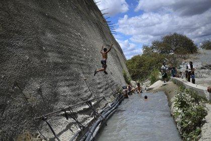 Un niño salta a una zanja que canaliza el agua de un túnel abandonado en Caracas, Venezuela, el 6 de junio de 2020. Hacía mucho que los obreros habían dejado de trabajar en un túnel de autopista que cruzaba la montaña. Sin embargo, el agua de manantial seguía acumulándose dentro del viaducto y discurría, malgastada, por delante de las casas. (AP Foto/Matías Delacroix)