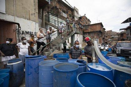 """Un residente llena un recipiente con el agua distribuida por un camión cisterna gubernamental en el vecindario de Petare, en Caracas, Venezuela, el 15 de junio de 2020. El gobierno de Nicolás Maduro ha acusado a sus enemigos políticos de sabotear estaciones de bombeo, y recientemente celebró la compra de una flota de 1.000 camiones """"súper cisterna"""" a China para llevar agua a los residentes. (AP Foto/Ariana Cubillos)"""