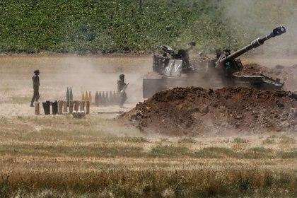 Un soldado israelí lleva un proyectil cerca de una unidad de artillería militar, visto desde el lado israelí de la frontera con la Franja de Gaza este domingo 16 de mayo. La artillería israelí y los bombardeos aéreos destruyeron una vasta red de túneles de los terroristas de Hamas en los últimos días (Reuters)
