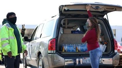 Una mujer cargando botellas de agua en su vehículo (JUSTIN SULLIVAN / GETTY IMAGES NORTH AMERICA / AFP)