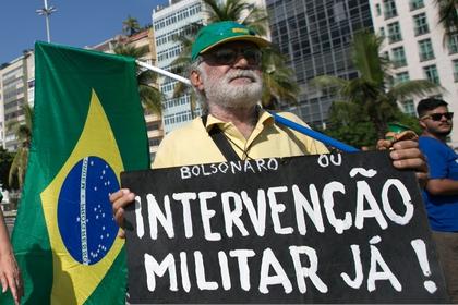 """Un hombre muestra un cartel con la consigna """"Bolsonaro o intervención militar ya"""", durante una marcha en Rio de Janeiro en marzo de 2019 (Reuters)"""