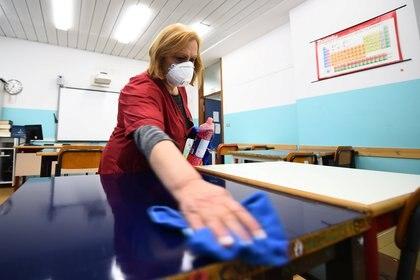 Una empleada desinfecta un aula en la escuela secundaria Piero Gobetti en Turín, Italia, como parte de las medidas para tratar de contener un brote de coronavirus (Reuters)