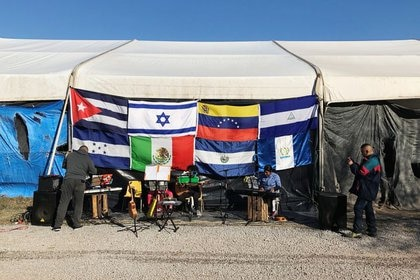 Niños migrantes que viajaron con sus padres en busca de asilo en Estados Unidos tocan una canción en un campamento en Matamoros (Foto: REUTERS / Laura Gottesdiener)