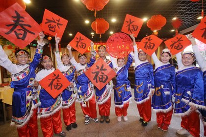 Estudiantes posan en Beijing con decoraciones típicas del Año Nuevo Lunar, en esta imagen de archivo (AFP)