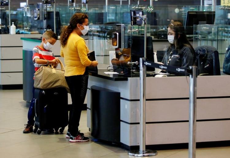 Foto de archivo. Pasajeros hacen trámites de inmigración usando tapabocas para evitar el contagio con coronavirus en el aeropuerto Intrenacional El Dorado de Bogotá, Colombia, 5 de marzo, 2020. REUTERS/ Leonardo Muñoz. NO VENTA NO ARCHIVO