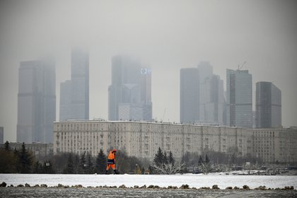 Un empleado municipal limpia la nieve con la ciudad de Moscú (Rusia) de fondo. Alexander NEMENOV / AFP