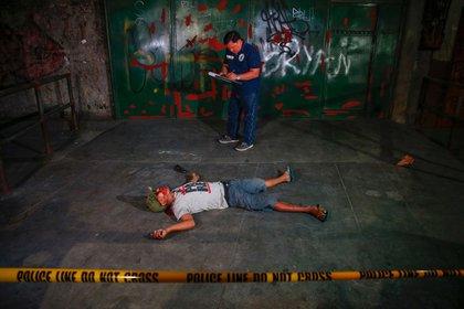 El investigador policial Glenzor Vallejo toma notas tras encontrar el cuerpo de un sospechoso asesinado en un tiroteo. La policía identificó a la víctima sólo por su alias, Gilbert. Como con muchos otros asesinatos, los oficiales dijeron que se encontraron sobres de polvo blanco y un arma en el cuerpo (Reuters)