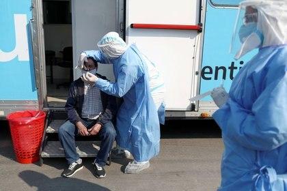 Un trabajador de la salud toma muestra de un hombre que tenía síntomas de coronavirus (COVID-19), en Villa Fiorito, en las afueras de Buenos Aires, Argentina (REUTERS/Agustin Marcarian)