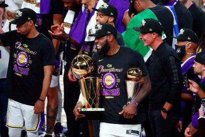 FILE PHOTO: Oct 11, 2020; Lake Buena Vista, Florida, USA; Los Angeles Lakers forward LeBron James (23) smiles while holding the MVP and Finals trophies after game six of the 2020 NBA Finals at AdventHealth Arena. The Los Angeles Lakers won 106-93 to win the series. Mandatory Credit: Kim Klement-USA TODAY Sports/File Photo
