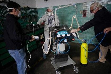 Marcio Larrosa, (Izq) Marcelo Larrosa, (C) y el cardiólogo Robert Canessa con un respirador que desarrollaron y que es impulsado por un motor de limpiaparabrisas en Montevideo, el 9 de abril de 2020 (REUTERS/Mariana Greif)