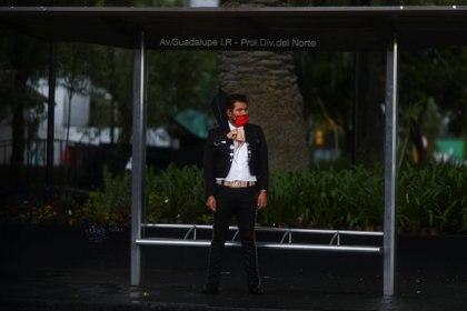 Un mariachi con mascarilla espera un autobús mientras continúa el brote de la enfermedad por coronavirus en Ciudad de México (Foto: REUTERS)