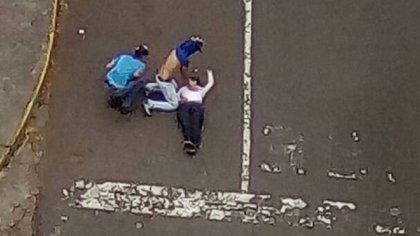Paola Andreína yace en el suelo tras recibir un impacto de bala. Sus amigos tratan de reanimarla. Será en vano