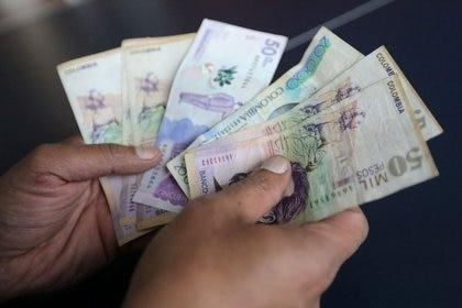 FOTO DE ARCHIVO. Un trabajador cuenta billetes de peso colombiano en una tienda en Bogotá, Colombia. 28 de diciembre de 2018. REUTERS/Luisa González