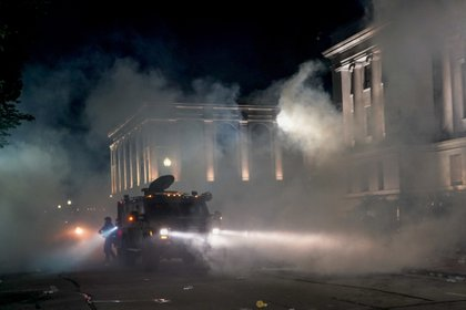 La ira por el tiroteo de un hombre negro por parte de la policía se extendió a las calles de Kenosha por segunda noche el lunes, y la policía volvió a disparar gases lacrimógenos contra cientos de manifestantes que desafiaron el toque de queda, arrojaron botellas y dispararon fuegos artificiales a las fuerzas del orden que custodiaban el juzgado. (AP Photo/Morry Gash)