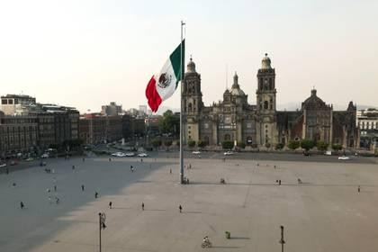 Personas caminan alrededor de la bandera mexicana en el Zócalo en la Ciudad de México, que luce con pocas personas en medio del brote de coronavirus el 25 de marzo de 2020 (REUTERS/Henry Romero)