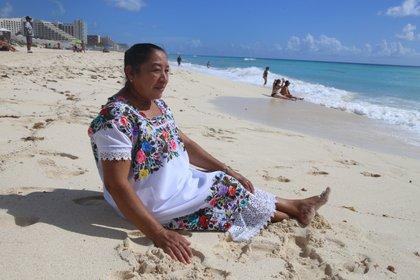 María del Socorro Balan Ucan llamó la atención de los visitantes de la playa no sólo por su colorido hipil bordado sino por la forma en la que disfrutaba conocer el mar. (Foto: EFE)