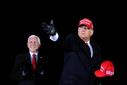 El presidente de Estados Unidos, Donald Trump, reparte gorras a sus seguidores junto al vicepresidente Mike Pence, mientras realiza un mitin de campaña en el Aeropuerto Internacional Gerald R. Ford en Grand Rapids, Michigan. REUTERS/Carlos Barria