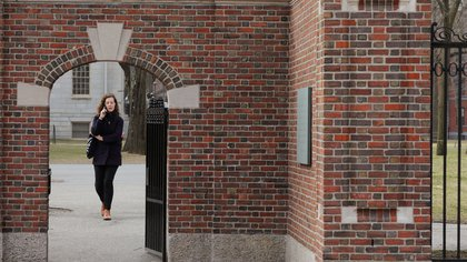 A woman walks through a gate to the Yard at Harvard University, after the school asked its students not to return to campus after Spring Break and said it would move to virtual instruction for graduate and undergraduate classes, in Cambridge, Massachusetts, U.S., March 10, 2020.   REUTERS/Brian Snyder
