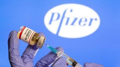"""Una mujer sostiene un pequeño frasco con la etiqueta de """"Vacuna contra la COVID-19"""" y frente al logo de Pfizer que aparece en esta ilustración tomada el 30 de octubre de 2020. REUTERS/Dado Ruvic"""