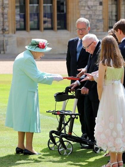 La reina le hace entrega de la medalla insignia