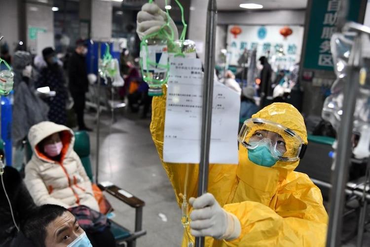 Un trabajador médico ajusta una bolsa de goteo para un paciente en un hospital de Wuhan (China Daily via REUTERS)