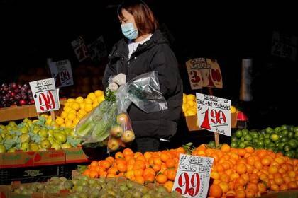 Imagen de archivo de una mujer que utiliza mascarilla y guantes comprando frutas en medio del brote de coronavirus, en Brooklyn, Nueva York, EEUU, Mayo 11, 2020. REUTERS/Brendan McDermid