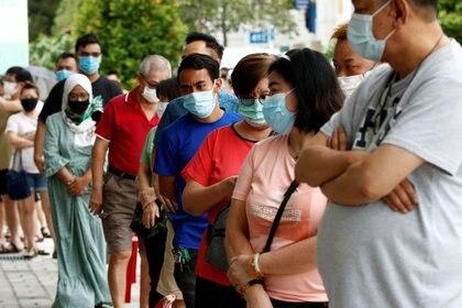 Votantes usan mascarillas mientras hacen fila en una mesa electoral durante las elecciones generales, en medio del brote de la enfermedad del coronavirus (COVID-19), en Singapur. 10 de julio de 2020. REUTERS/Edgar Su