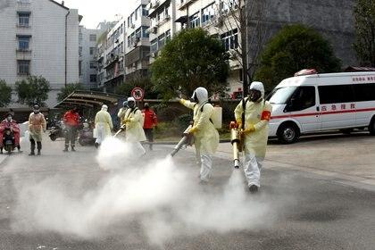 Voluntarios realizan desinfecciones en Taizhou, en la provincia de Zhejiang, China - REUTERS